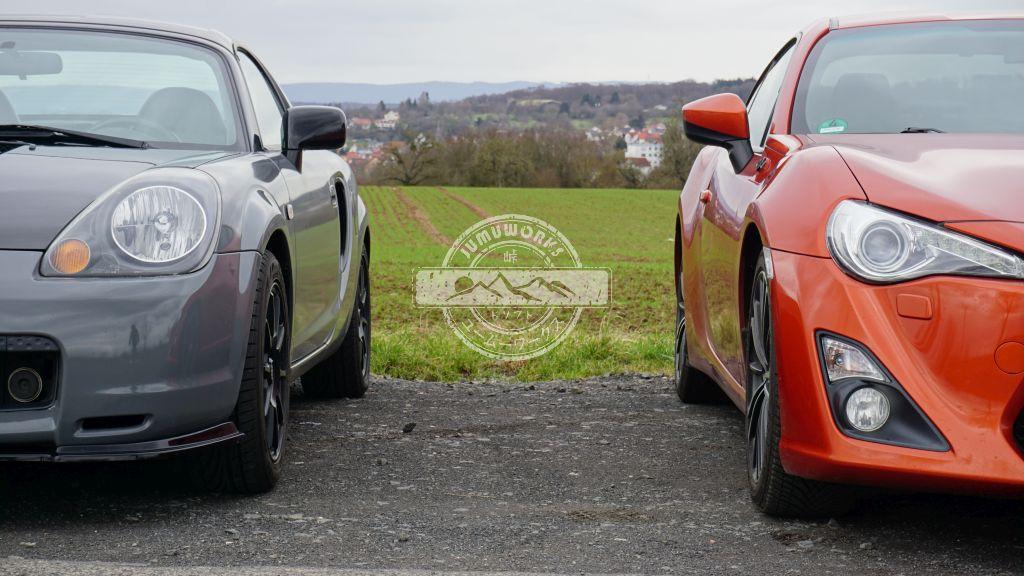 Ein orangefarbener GT86 und ein grau-schwarzer MR2 frontal vor einer grünen Wiese.